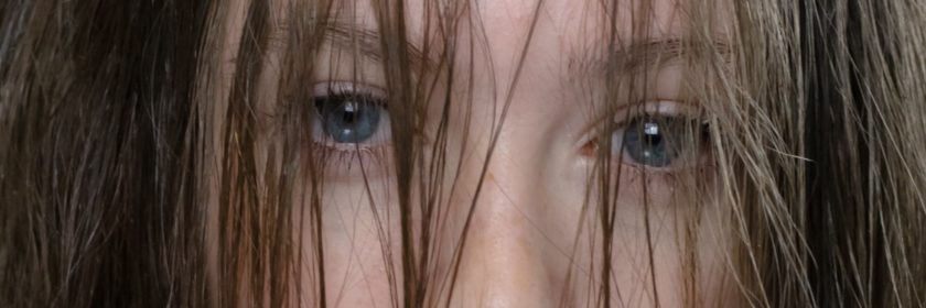 eyes of a girl with hair over her eyes