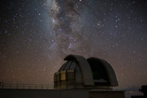 night time view of an observatory with the milky way in the background