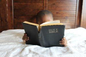 child in bed reading a bible