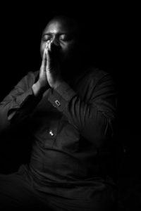 black and white photo of man praying
