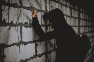 man in hoodie facing a wall