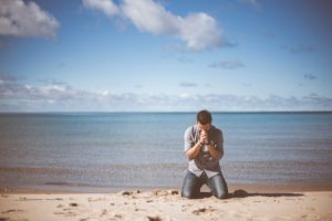 man kneeling on the beach, praying