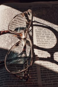 reading glasses on top of an open Bible