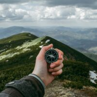 photo of landscape with hand holding a compass