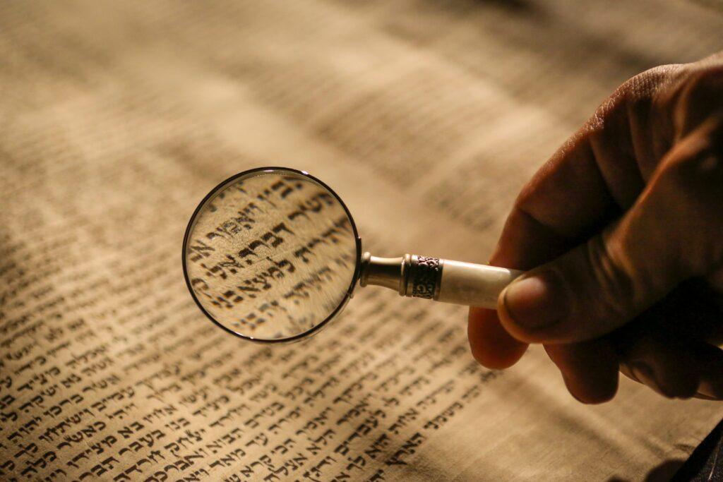 had holdinga magnifying glass over copy of the Torah