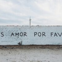 brick wall with the text written: more love please, in Spanish