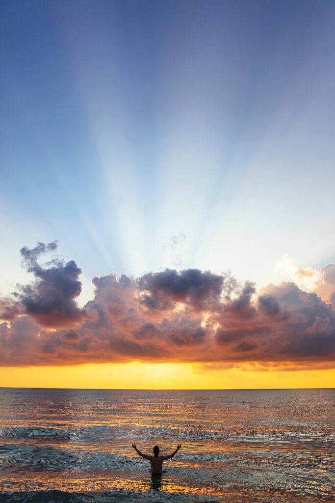 man at beach watching sunrise