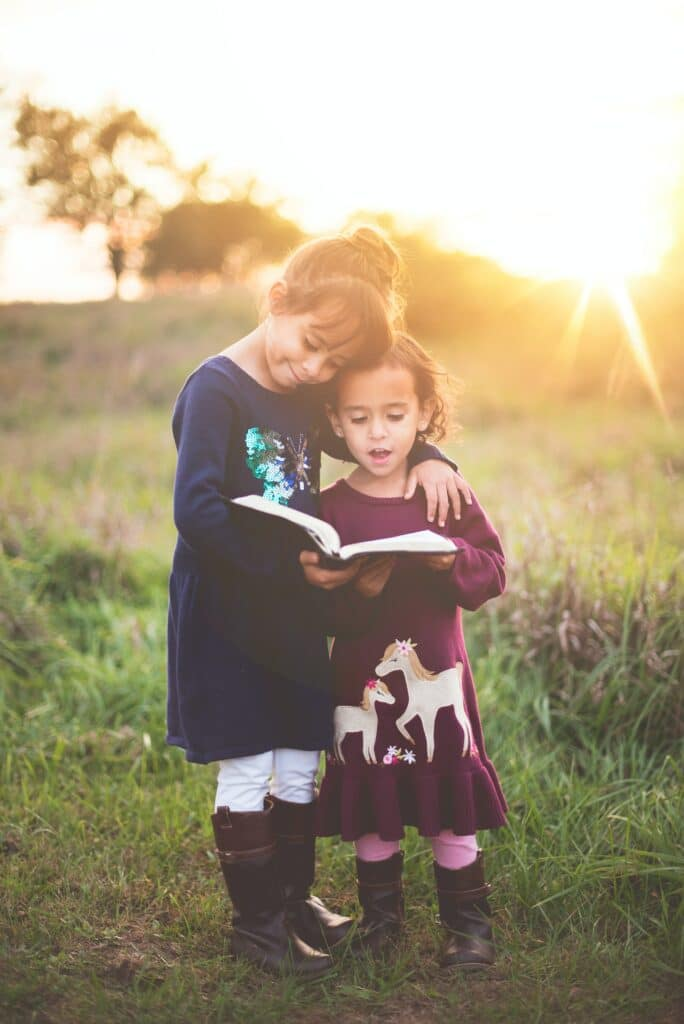photo of a little girl helping another little girl read