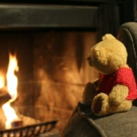 photo of a teddy bear looking at a fireplace