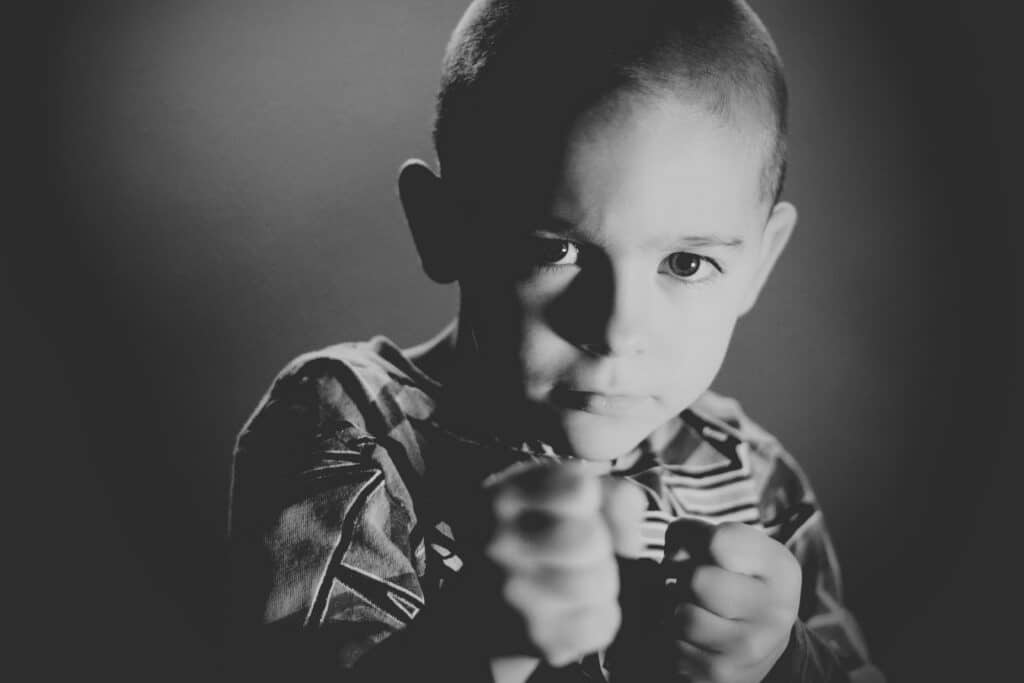 photo of child holding fists up like a boxer