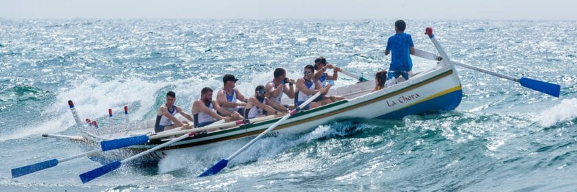 photograph of a rowing team on a boat in the sea